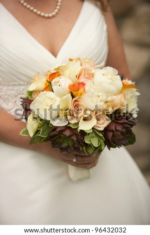 Bride holding wedding bouquet of colorful flowers - stock photo