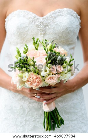 Bride Holding Wedding bouquet of roses