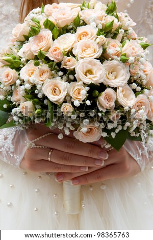 Bride holding wedding bouquet of roses in his hands