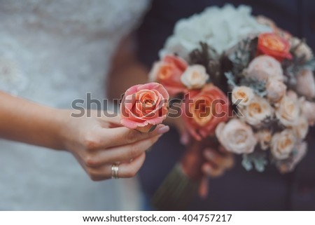Bride holding wedding bouquet of various flowers, film like color effect