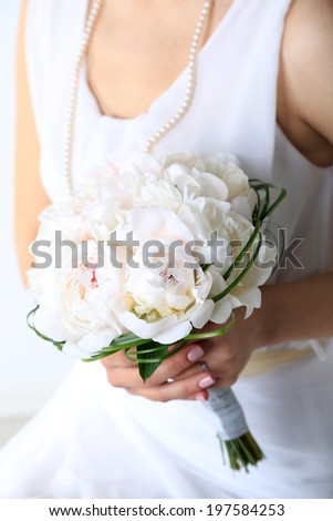 Bride holding wedding bouquet of white peonies, close-up