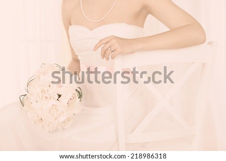 Bride holding wedding bouquet of white peonies, close-up, on light background - stock photo