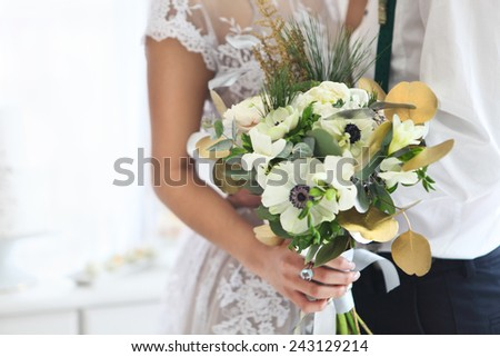 Bride holding wedding bouquet with ranunculus, freesia, roses and white anemone  - stock photo