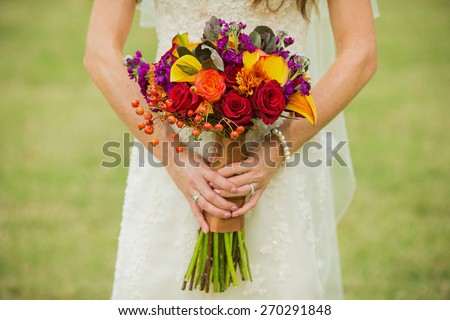 Bride holding wedding bouquet with Rose Hips, Smokebush, and yellow Calla Lilies - stock photo