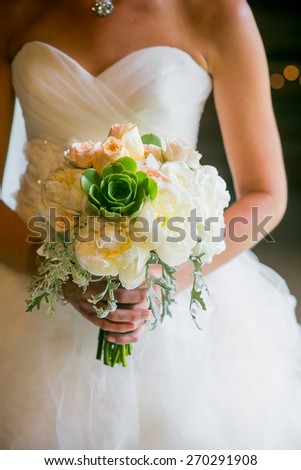 Bride holding wedding bouquet with Roses, Echeveria, Dusty Miller, Peonies, and Queen Anne'??s Lace flowers - stock photo
