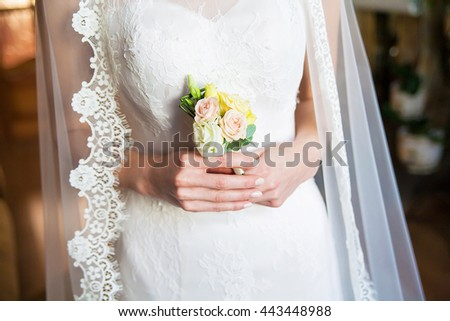Bride holding wedding boutonniere in the hands. Bride morning
