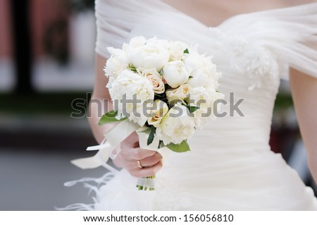 Bride holding wedding flowers bouquet - stock photo