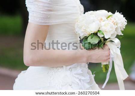 Bride holding wedding flowers bouquet - stock photo