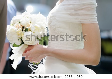 Bride holding wedding flowers bouquet, closeup photo