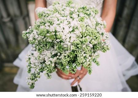 Bride holding white lilac wedding bouquet; Lilac wedding bouquet - stock photo