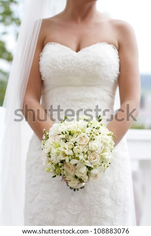 Bride holding white wedding bouquet of roses and love flower