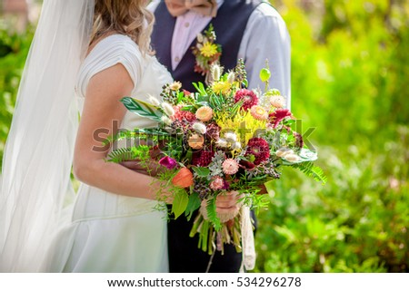 Bride holding wildflower bouquet groom kissing