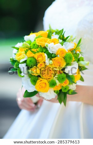 bride holds a wedding bouquet,  yellow roses