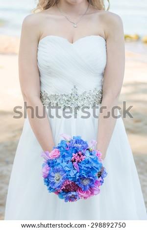 Bride holds blue pink wedding bouquet - stock photo