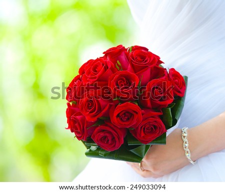 bride holds bouquet of red roses - summer green background - stock photo