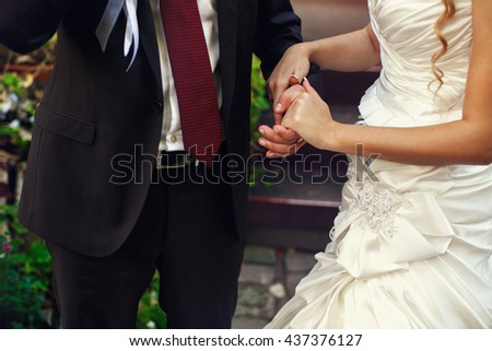 Bride holds groom's hand tenderly standing outdoors