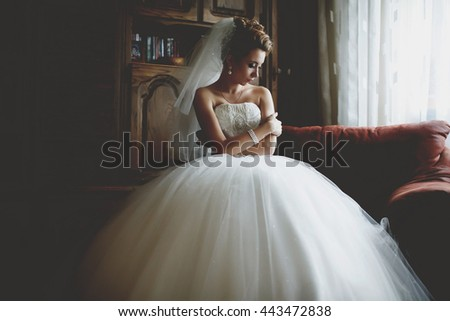 Bride holds her shoulders while sitting in the big red chair