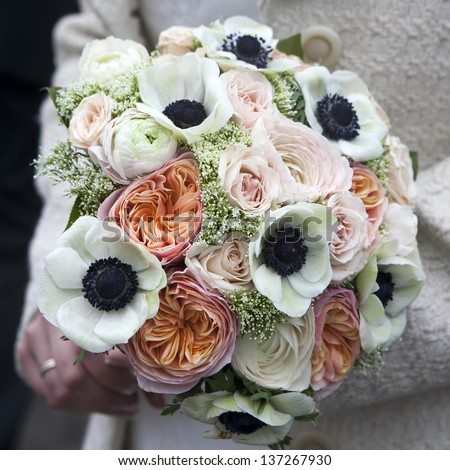 Bride holds wedding bouquet of pink roses and white anemone and pink ranunculus lying on wooden floor - stock photo