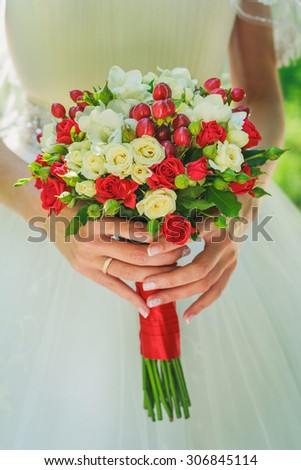 Bride holds wedding bouquet with little red roses - stock photo