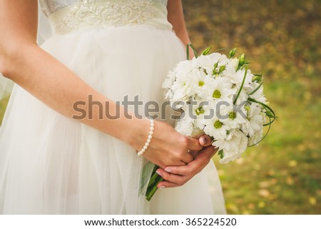 Bride holds wedding bouquet with white chamomiles