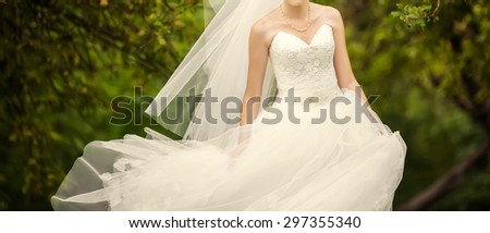 bride in a beautiful dress walks in the park