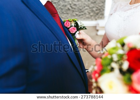bride in a dress fixes buttonhole groom in a blue suit