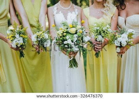 bride in a white dress and bridesmaids dresses are yellow and are holding bouquets of yellow flowers and greenery - stock photo