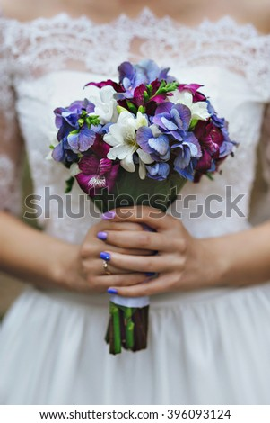 bride in a white dress holding a wedding bouquet of flowers.