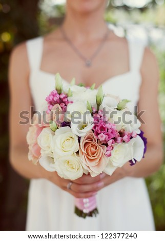 Bride in a white dress in summer green park with a bouquet in hand