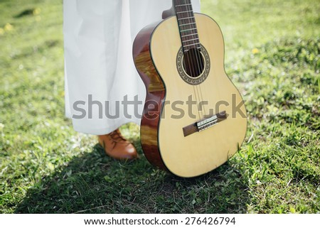 bride in a white vintage dress and brown leather boots with a guitar standing on the green grass - stock photo