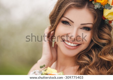 Bride in blooming apple trees. Woman in flower wreath and wedding bouquet in hands. Beautiful bride in wedding dress posing in a blooming apple garden. Spring mood. Young woman outdoors