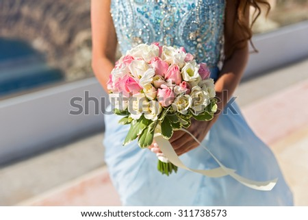 Bride in blue dress with bouquet of flowers. Greece, island of Santorini