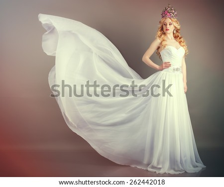 Bride in flying wedding dress in the studio on a gray background - stock photo