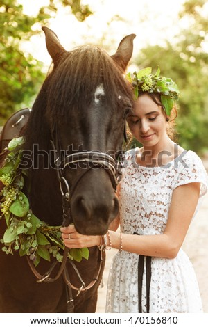 Bride  in forest with horses. Beautiful woman and a dark horse.
