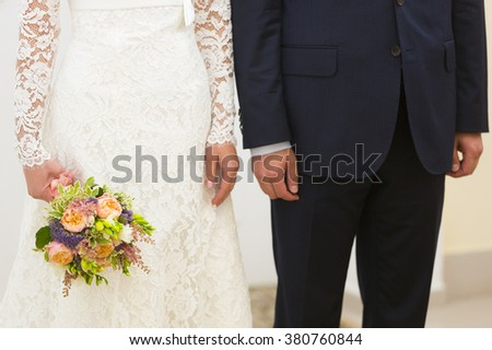 Bride in lace wedding dress with wedding bouquet and groom