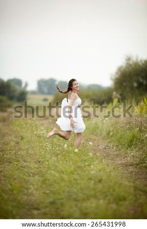 bride in national costume jump in meadow