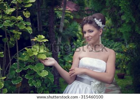 Bride in the garden. Wedding day. - stock photo