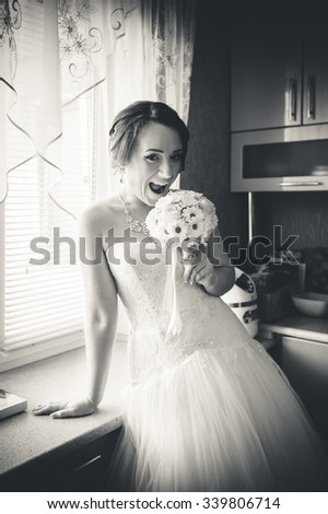 Bride in the interior of the house by the window