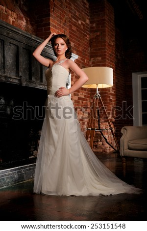 Bride in wedding dress in the studio next to the fireplace.