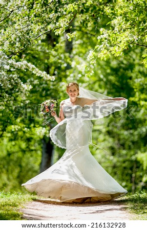 Bride in wedding dress is spinning, among apple blossom - stock photo