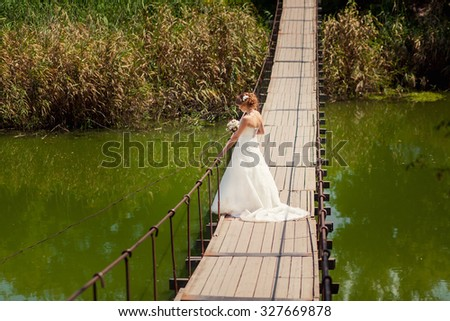 Bride in wedding dress looking at the river on suspension bridge