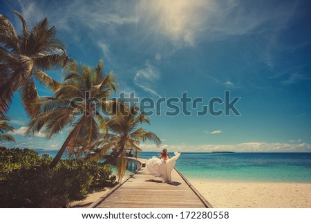 bride in wedding dress running and having fun on tropical island of maldives - stock photo
