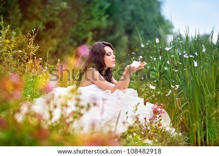 bride in wedding dress sits in a grass and blows off fuzz from hands - stock photo