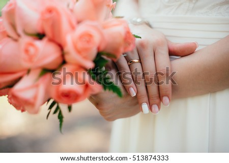 bride in white dress on nature with flowers in their hands
