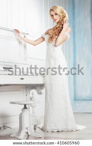 Bride in white dress posing near a piano. - stock photo