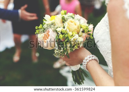 Bride in white dress with luxury bouquet on her wedding ceremony outdoors. - stock photo