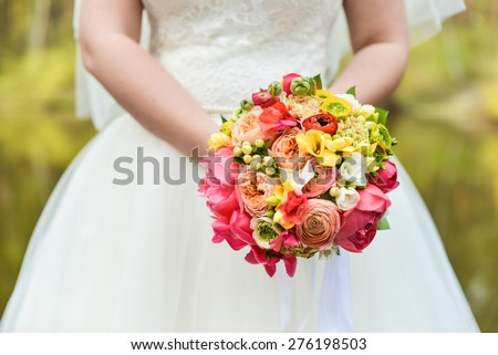 bride in white wedding dress holding a bouquet of bright flowers on green background