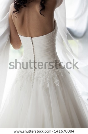 bride in white wedding dress looking in window - stock photo