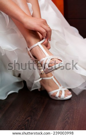 Bride in white wedding dress putting on white shoes  - stock photo