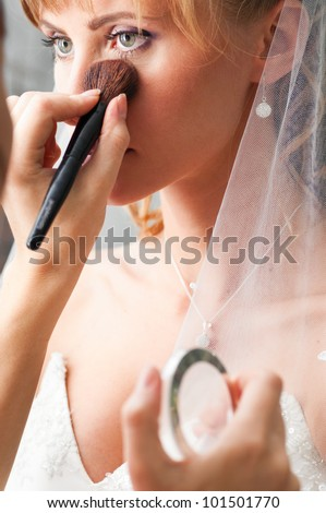 bride is doing make up for wedding celebration - stock photo